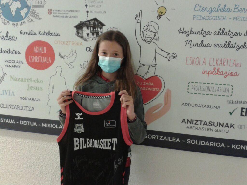 alumna recogiendo premio camiseta Bilbao Basket